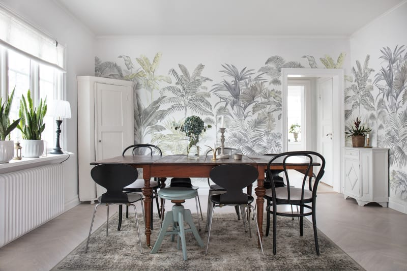 A bright dining room with a botanical wallpaper.